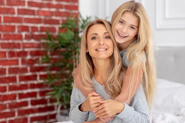 Encantadora hija abrazando a su madre