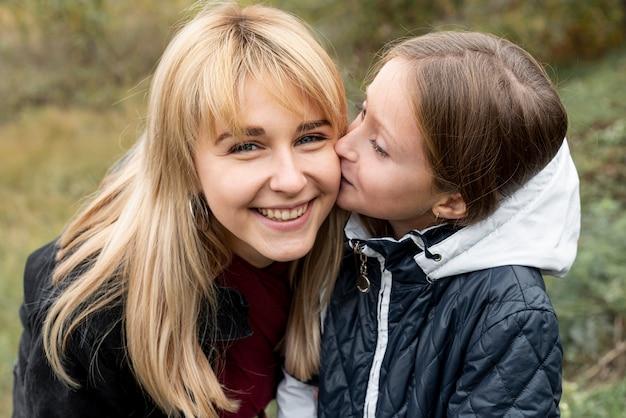 Encantadora hija besando a su madre