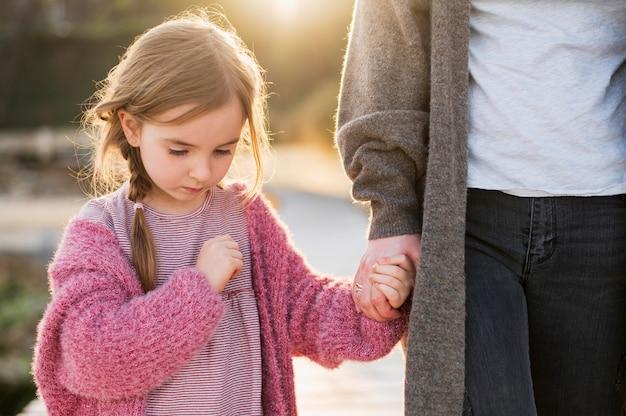 Encantadora hija y madre cogidos de la mano