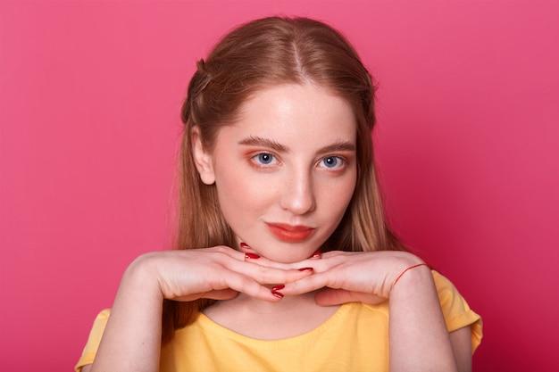 Encantadora joven adolescente, vestida con una camiseta amarilla informal, tomados de la mano bajo la barbilla, pensando en algo importante. mujer con cabello largo y liso