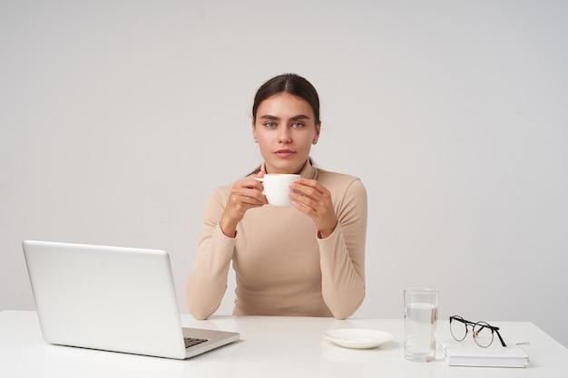 Encantadora joven y bella dama morena de ojos azules sosteniendo una taza de té en las manos levantadas y mirando a la cámara con rostro tranquilo, vestida con ropa formal mientras posa sobre una pared blanca