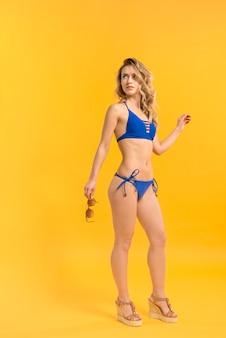 Encantadora joven en bikini posando con gafas de sol