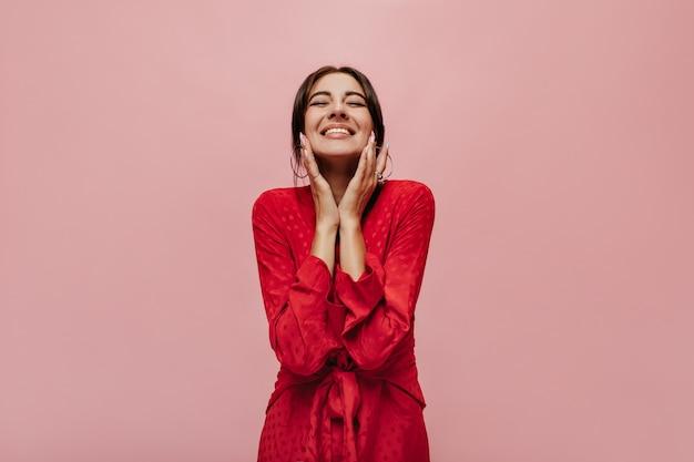 Encantadora joven de buen humor con aretes frescos en traje rojo moderno posando con los ojos cerrados y sonriendo en la pared rosa