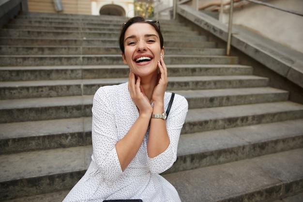 Encantadora joven dama morena atractiva con peinado casual sosteniendo la cara con las manos levantadas y mirando felizmente, sentada sobre las escaleras de la ciudad en vestido blanco de lunares