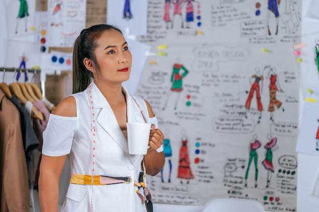 Encantadora joven diseñadora de moda sosteniendo la taza de café en la mano y mirando hacia adelante en la sastrería
