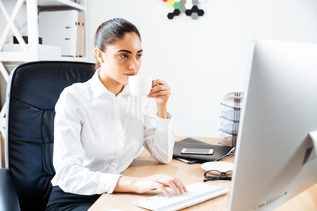 Encantadora joven empresaria usando laptop y bebiendo una taza de café mientras está sentado en el escritorio de la oficina