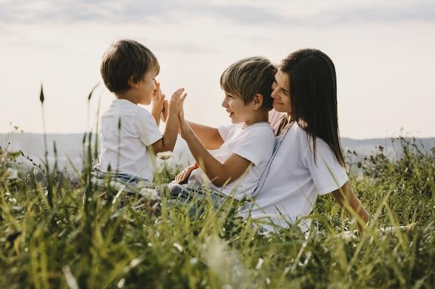Encantadora joven madre se divierte con sus pequeños hijos