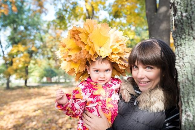 Encantadora joven madre sostiene en sus brazos a una niña bonita con una corona de hojas de otoño de arce amarillo en la cabeza mientras camina en el parque. concepto de otoño