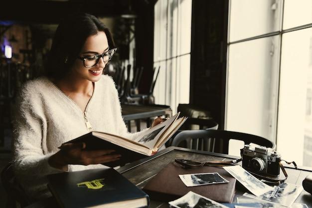 Encantadora joven mira viejos álbumes de fotos sentados en un café