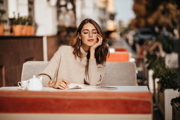 Encantadora joven morena con labios rojos, gafas y suéter beige, aprendiendo algo del cuaderno, tomando una taza de té en la terraza de un café en la cálida ciudad soleada
