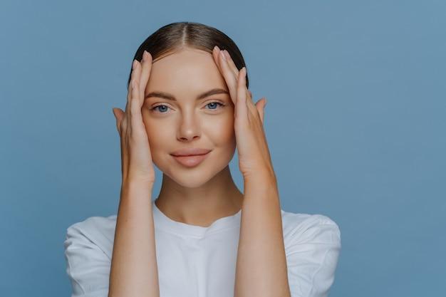 Encantadora joven morena modelo femenino toca la cara disfruta de la suavidad de la piel tiene maquillaje natural