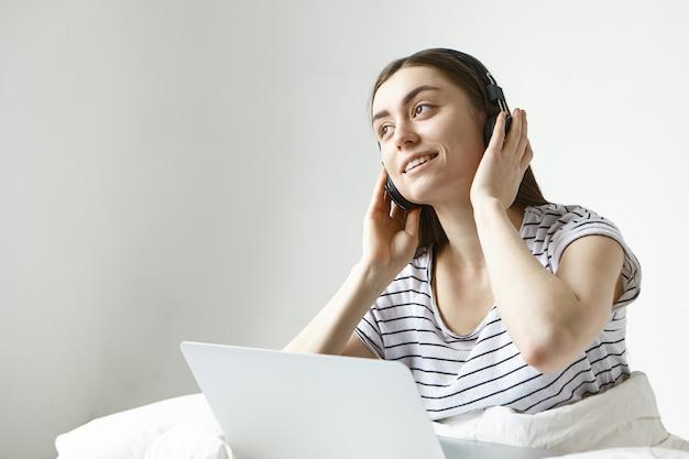 Encantadora joven mujer de cabello oscuro pasar la mañana del fin de semana en la cama con un portátil, disfrutando de nuevas pistas musicales