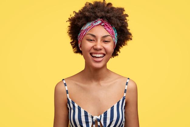 Encantadora joven negra con corte de pelo afro sonríe positivamente