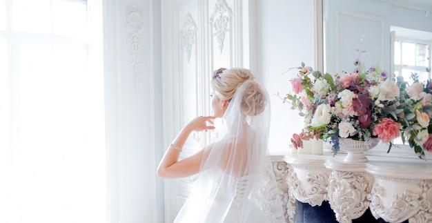 Encantadora joven novia en lujoso vestido de novia. chica guapa, estudio fotográfico