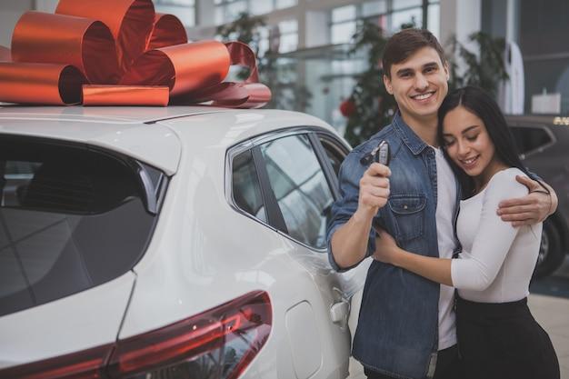 Encantadora joven pareja casada comprando un auto nuevo juntos
