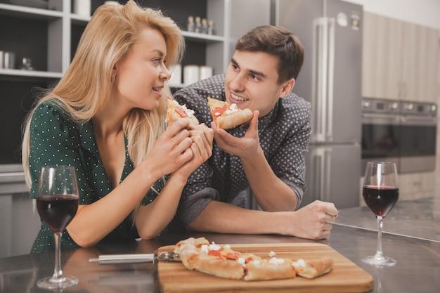 Encantadora joven pareja comiendo pizza juntos en la cocina