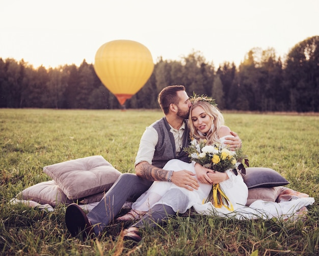 Encantadora joven pareja en vestidos de novia en estilo bohho, en un campo con un globo