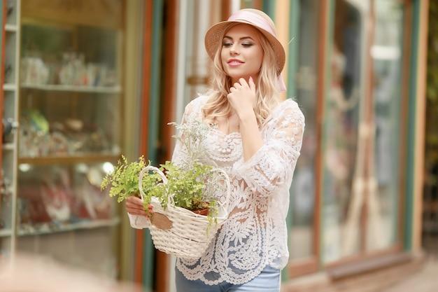 Encantadora joven con sombrero de verano descansando en el café al aire libre cara apoyada con la mano y esperando amigo.