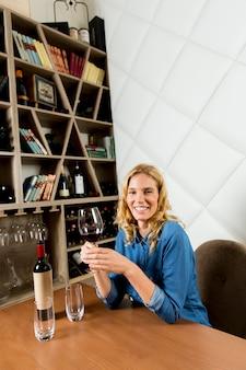 Encantadora joven sonriente bebe vino tinto y se sienta en el restaurante vintage