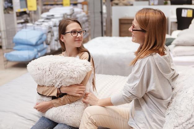 Encantadora madre e hija comprando muebles de dormitorio juntas