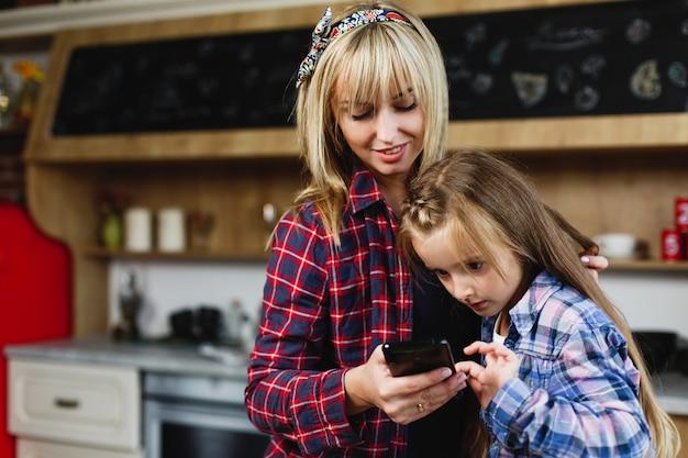 Encantadora madre e hija en las mismas camisetas miran algo en un teléfono inteligente