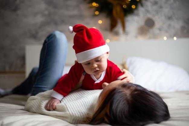 Encantadora madre mira a su pequeño hijo pequeño y sonriendo en el fondo de árboles de navidad y guirnaldas en la casa