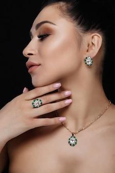 Encantadora modelo con cabello oscuro muestra ricos aretes de oro, collar y anillo