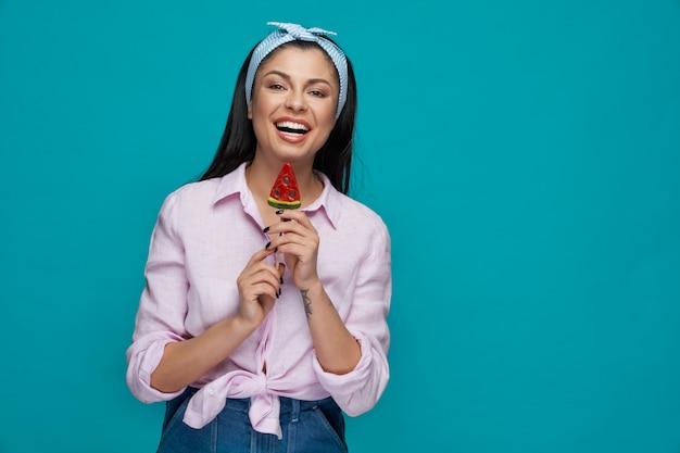 Encantadora morena comiendo sabroso helado y sonriendo