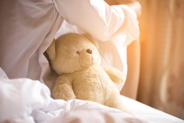 Encantadora morena sentada usa camisa blanca pijama en la cama con su oso de peluche marrón.