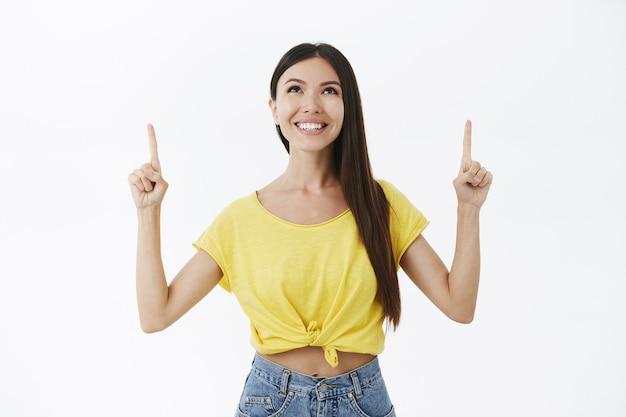 Encantadora mujer adulta despreocupada con cabello largo hermoso en camiseta amarilla de moda levantando las manos apuntando y mirando hacia arriba