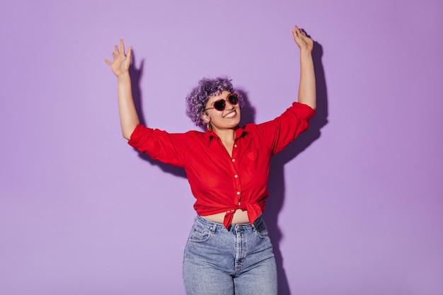 Encantadora mujer adulta con pelo corto y gafas de buen humor con ropa elegante levanta las manos y sonríe.