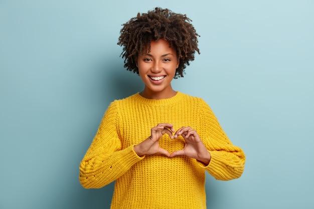Encantadora mujer con un afro posando con un suéter rosa