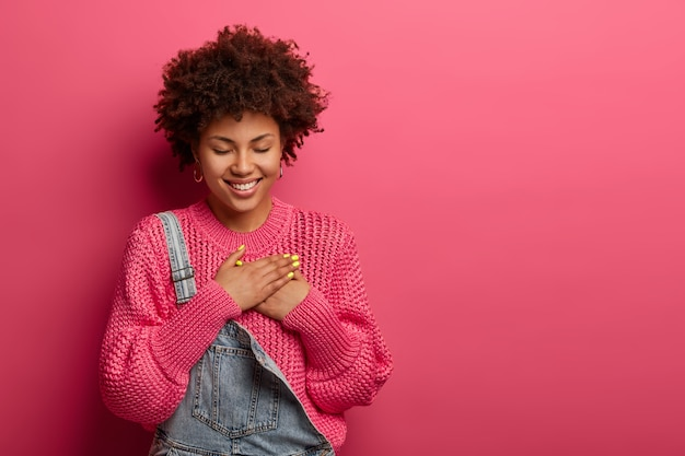 Encantadora mujer afroamericana alegre presiona las palmas de las manos al corazón, tiene expresión agradecida