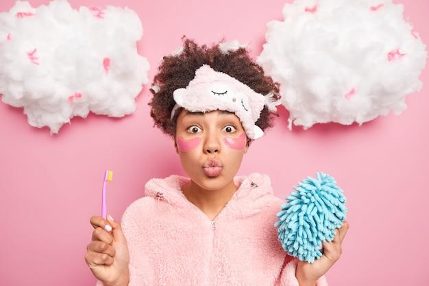 Encantadora mujer afroamericana mantiene los labios doblados quiere besarte sostiene cepillo de dientes y esponja de baño vestida con ropa de dormir plantea interior