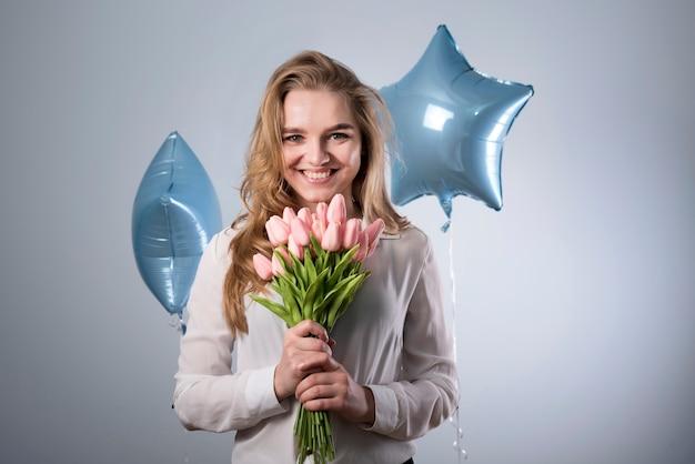 Encantadora mujer alegre con ramo de flores y globos.