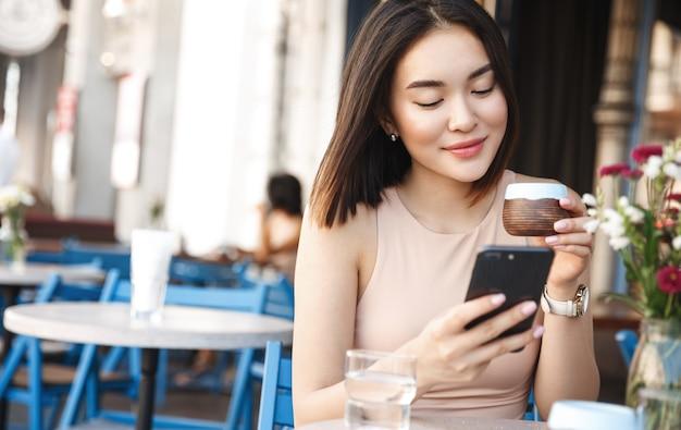 Encantadora mujer asiática con hermosa sonrisa leyendo buenas noticias en el teléfono móvil durante el descanso en la cafetería.