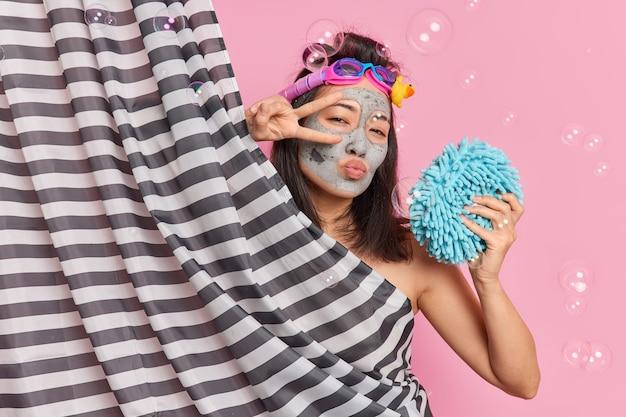 Encantadora mujer asiática romántica hace gesto de paz sobre los ojos mantiene los labios doblados