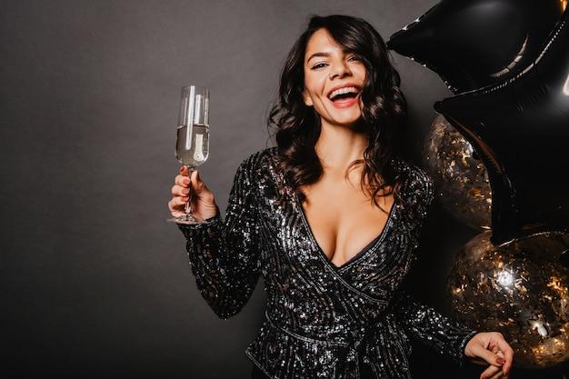 Encantadora mujer bronceada levantando copa de vino