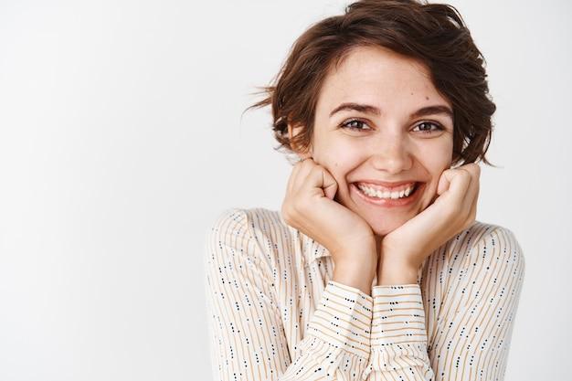 Encantadora mujer caucásica se inclina la cara en las manos y sonriendo feliz de pie sobre la pared blanca en blusa casual