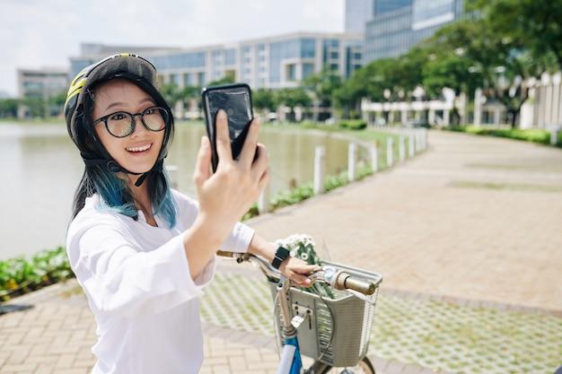 Encantadora mujer china joven emocionada en casco de bicicleta tomando selfie después de andar en bicicleta