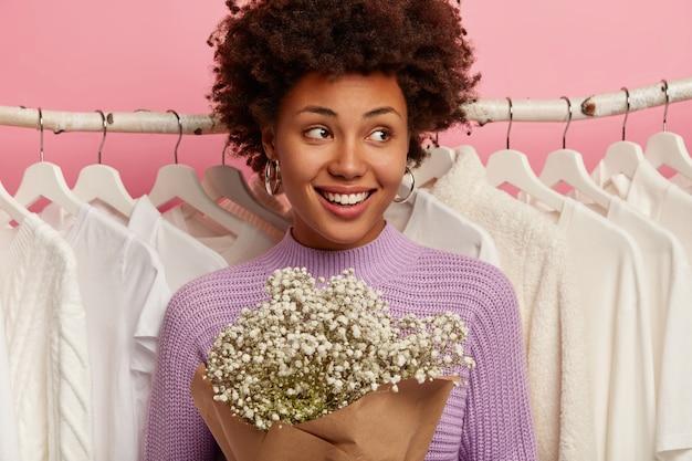 Encantadora mujer complacida tiene el cabello rizado, tiene una sonrisa con dientes, usa un suéter morado casual, sostiene un ramo, se para contra un suéter blanco en los estantes