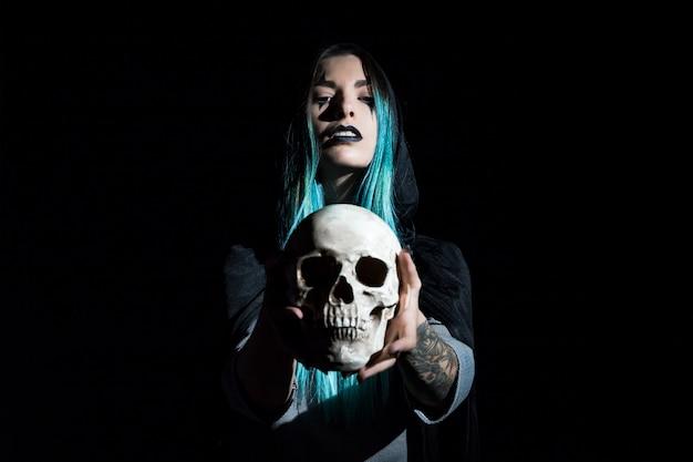 Encantadora mujer con cráneo humano