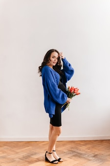 Encantadora mujer embarazada en cardigan azul tiene ramo de tulipanes. feliz señorita en vestido negro posa con flores en aislado.