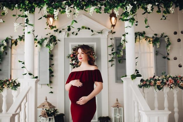 Encantadora mujer embarazada en marsala vestido posando
