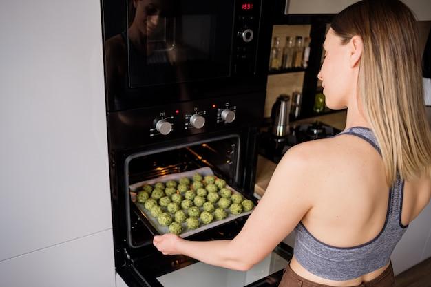 Encantadora mujer en forma puso en el horno una bandeja con falafel