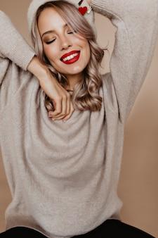 Encantadora mujer francesa con labios rojos posando con los ojos cerrados