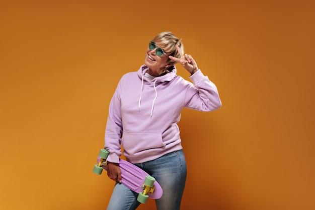 Encantadora mujer fresca con peinado moderno rubio en gafas verdes y sudadera con capucha rosa de gran tamaño sonriendo, mostrando el signo de la paz y posando con patineta sobre fondo naranja.