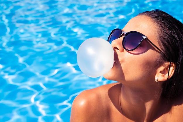 Encantadora mujer con gafas de sol soplando burbujas con chicle en la piscina al aire libre