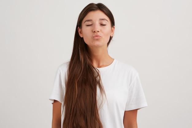 Encantadora mujer, hermosa niña con cabello largo oscuro, vestida con camiseta blanca