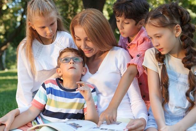 Encantadora mujer hermosa que disfruta leyendo a sus estudiantes al aire libre en el parque